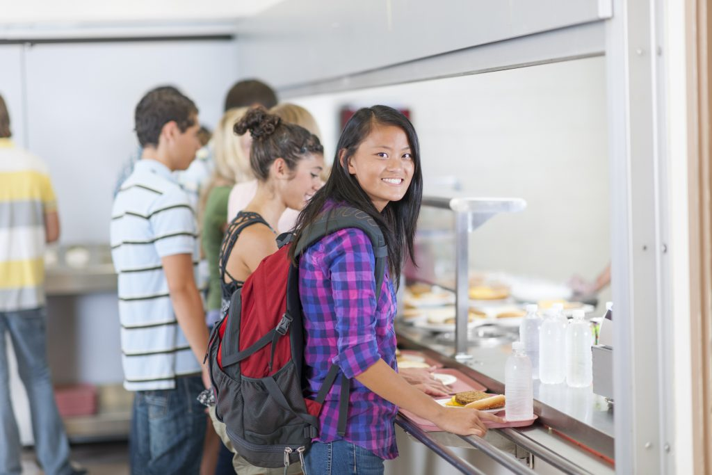 Diverse high school students eating lunch in the cafeteria