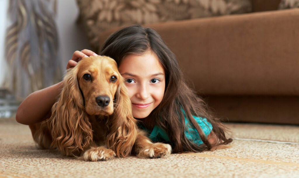 A girl lies on the floor with a dog